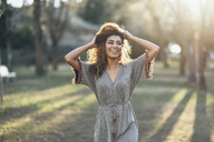 Portrait of happy young woman in a park at backlight - JSMF00092
