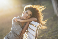 Portrait of young woman relaxing on bench in a park at sunset - JSMF00101
