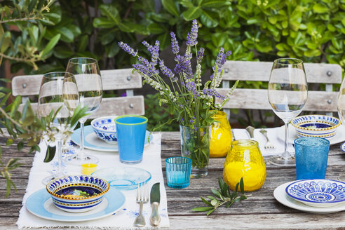 Garden table laid with colorful plates and bowls - GWF05467