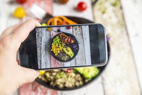 Girl taking photo of vegan Lunch bowl with cell phone, close-up - SARF03594
