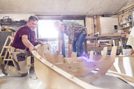 Male carpenters making wood boat in workshop - CAIF07057