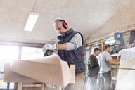 Senior carpenter using sander, sanding wood boat in workshop - CAIF07063