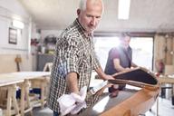Senior man finishing, wiping wood kayak in workshop - CAIF07066