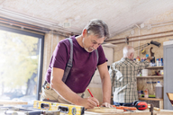 Male carpenter measuring and marking wood plank on workbench in workshop - CAIF07069