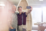 Proud, smiling male carpenters with camera phone taking selfie next too wood boat in workshop - CAIF07072