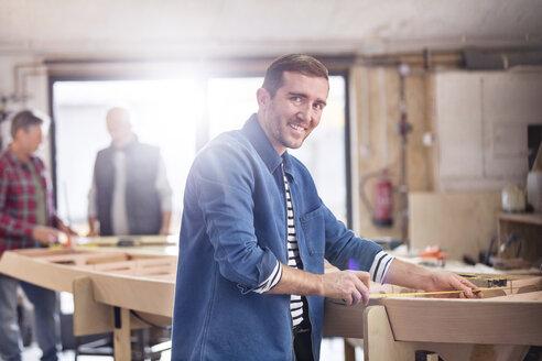 Portrait smiling male carpenter measuring wood on boat in workshop - CAIF07081
