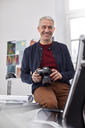 Portrait smiling, confident male photographer with digital camera in office - CAIF07093
