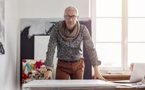 Portrait confident male photographer standing over canvas in art studio - CAIF07099