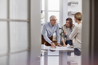 Architects reviewing, discussing blueprints in conference room meeting - CAIF07114