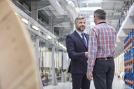 Business owner and supervisor handshaking in fiber optics factory - CAIF07207