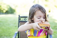 Preschool girl eating messy cheeseburger on patio - CAIF07231