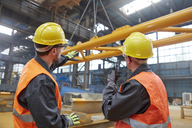 Male workers watching equipment being raised in factory - CAIF07258