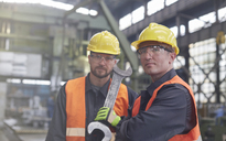 Portrait confident, tough male workers with large wrench in factory - CAIF07282