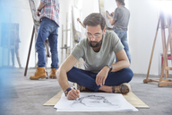 Male artist sitting cross-legged sketching on floor in art class studio - CAIF07294