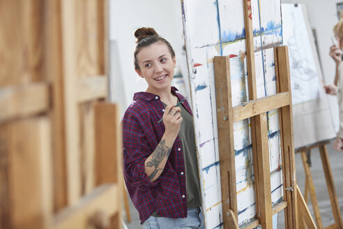 Female artist painting at easel in art class studio - CAIF07300