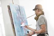 Male artist painting at easel in art studio - CAIF07306