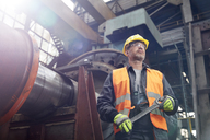 Confident male worker holding wrench in factory - CAIF07339