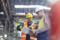 Male foreman and worker with clipboard talking in factory - CAIF07345