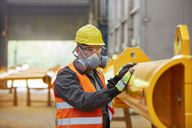 Male worker wearing protective mask in factory - CAIF07348