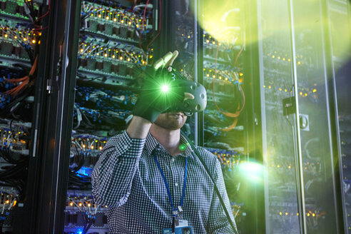 Male computer programmer using virtual reality simulator glasses and glowing glove in server room - CAIF07384