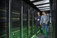 IT technicians walking and talking in dark server room - CAIF07423
