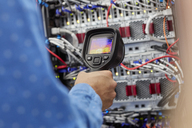 IT technician using diagnostic thermal imagining camera equipment in server room - CAIF07429