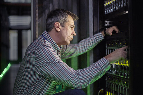 Focused male IT technician working at panel in dark server room - CAIF07432