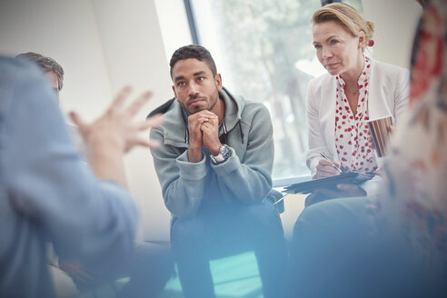 Attentive man and woman listening in group therapy session - CAIF07492
