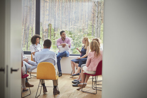 Woman talking in group therapy session - CAIF07504