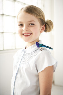 Portrait of happy little girl with toy bird on shoulder - FSF00993