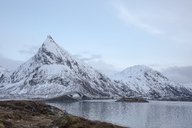 Snow covered mountains along cold lake, Lofoten Islands, Norway - CAIF07511
