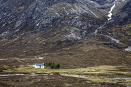 House in remote valley below craggy mountains, Glencoe, Scotland - CAIF07523
