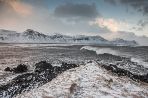 Snow covered mountain range over cold ocean, Budir, Snaefellsnes, Iceland - CAIF07535