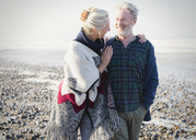 Senior couple hugging and walking on sunny rocky beach - CAIF07571