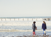 Brother and sister with nets in ocean surf - CAIF07574