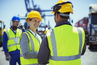 Business people wearing protective workwear talking - CAIF07649