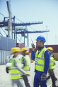 Worker using walkie-talkie near cargo containers - CAIF07652