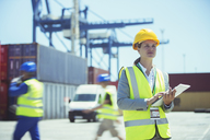 Businesswoman using digital tablet near cargo containers - CAIF07658
