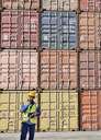 Worker using walkie-talkie near cargo containers - CAIF07664