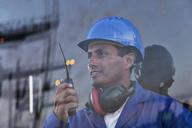 Worker holding walkie-talkie near window - CAIF07670
