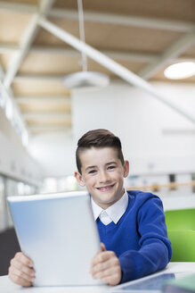 Portrait of smiling schoolboy with tablet pc - CAIF07682