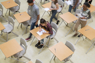 Elevated view of students writing their GCSE exam in classroom - CAIF07697