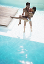 Couple relaxing in swimming pool - CAIF07736