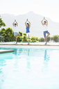 Men and woman practicing yoga at poolside - CAIF07745