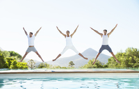 People jumping with arms and legs outstretched at poolside - CAIF07748