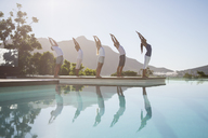 People practicing yoga at poolside - CAIF07754