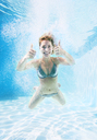 Woman giving thumbs up underwater in swimming pool - CAIF07763