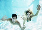 Portrait of smiling couple underwater in pool - CAIF07766