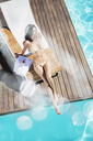 Woman relaxing poolside - CAIF07775