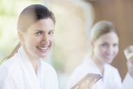 Woman using digital tablet at spa - CAIF07793